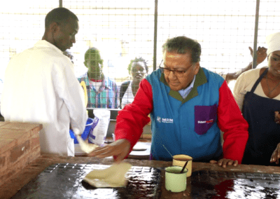 Dr. Chandaria cooking Chapati on the Kariobangi Community Cooker