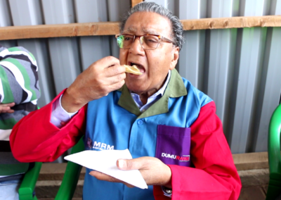 Dr. Chandaria eating Chapati cooked at Kariobangi Community Cooker